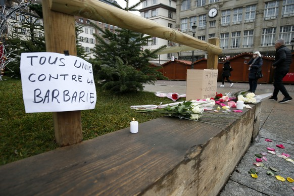 epa07225736 Flowers, candles and signs reading 'Tribute to the victims - Je Suis Strasbourg' and 'All against barbarity' are left where a person was killed during the Christmas Market shooting in Strasbourg, France, 12 December 2018. According to latest reports, three people were killed and several injured when a gunman opened fire at the Strasbourg Christmas market a day earlier. The suspect is reported to be at large and the motive for the attack is still unclear.  EPA/RONALD WITTEK