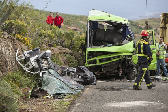 epa04118924 Members of the rescue services work near a minibus that crashed on Cazadores road, Gran Canaria Island, Spain, 10 March 2014. A Swiss tourist died and 17 people were injured, 8 of them seriously injured, due to the accident.  EPA/ANGEL MEDINA G.