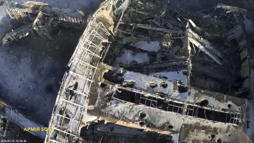 An aerial footage shot by a drone shows the terminal building of the Sergey Prokofiev International Airport damaged by shelling during fighting between pro-Russian separatists and Ukrainian government forces, in Donetsk, eastern Ukraine, seen in this still image taken January 15, 2015 handout video by Army.SOS, a Ukrainian group that supports the army by buying ammunition, food and supplies for soldiers. Fighting raged on Saturday at the main airport of Ukraine's city of Donetsk as separatists resumed attempts to break the tenuous grip of government forces on the complex and Kiev's military said three more Ukrainian soldiers had been killed. REUTERS/Army.SOS/Handout via Reuters (UKRAINE - Tags: POLITICS CIVIL UNREST CONFLICT) ATTENTION EDITORS - THIS PICTURE WAS PROVIDED BY A THIRD PARTY. REUTERS IS UNABLE TO INDEPENDENTLY VERIFY THE AUTHENTICITY, CONTENT, LOCATION OR DATE OF THIS IMAGE. FOR EDITORIAL USE ONLY. NOT FOR SALE FOR MARKETING OR ADVERTISING CAMPAIGNS. THIS PICTURE IS DISTRIBUTED EXACTLY AS RECEIVED BY REUTERS, AS A SERVICE TO CLIENTS. NO SALES. NO ARCHIVES