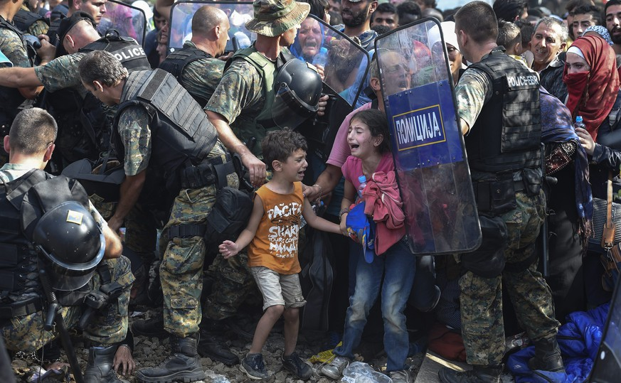 epa04990570 YEARENDER AUGUST 2015  Children cry as migrants wait on the Greek side of the border break through a cordon of Macedonian special police forces to cross into Macedonia, near the southern city of Gevgelija, The Former Yugoslav Republic of Macedonia, 21 August 2015. Macedonian police clashed with thousands of migrants attempting to break into the country after being stranded in no-man's land overnight, marking an escalation of the European refugee crisis for the Balkan country.  EPA/GEORGI LICOVSKI