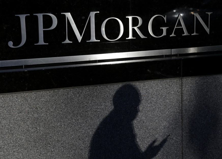 FILE - In this Nov. 19, 2013, file photo, the shadows of a pedestrian is cast under a sign in front of JPMorgan Chase & Co. headquarters in New York. JPMorgan Chase on Monday, Nov. 3, 2014 said the Justice Department has opened a criminal investigation into its foreign exchange business. (AP Photo/Seth Wenig, File)