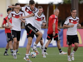 Germany's national soccer player Thomas Mueller, foreground left, warms up besides teammate Philipp Lahm during a training session in Santo Andre near Porto Seguro, Brazil, Tuesday, June 10, 2014. Germany will play in group G of the 2014 soccer World Cup. (AP Photo/Matthias Schrader)