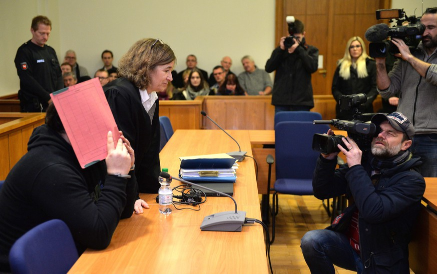 epa04575147 Former nurse Nils H., charged with multiple murders, sits next to his lawyer Ulrike Baumann (2-R) and hides his face with a folder in the district court in Oldenburg, Germany, 22 January 2015. The 38-year old is charged with three murders and two attempted murders. From 2003 to 2005 he allegedly injected patients at the Delmenhorster Intensive Station with a medication to cause serious heart and circulation problems.  EPA/CARMEN JASPERSEN