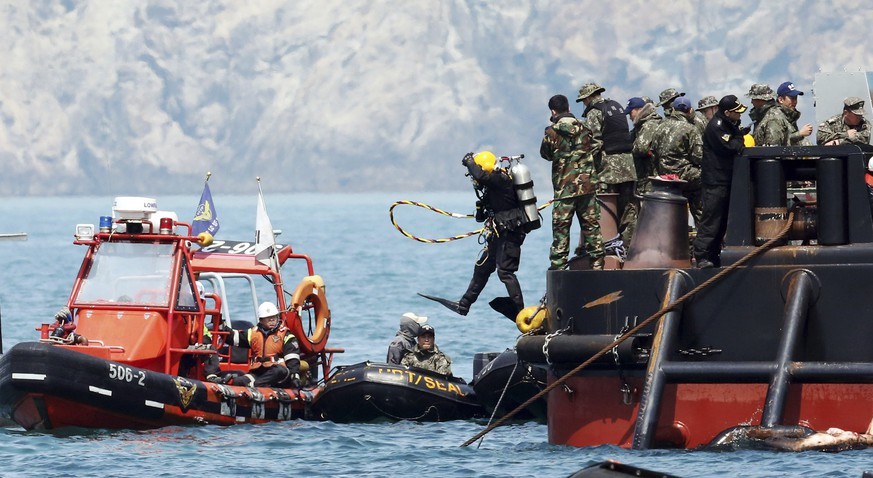 A diver jumps into the sea near an area where the capsized passenger ship Sewol sank during a rescue operation in Jindo April 25, 2014. The Sewol ferry, weighing almost 7,000 tons, sank on a routine trip from the port of Incheon, near Seoul, to the southern holiday island of Jeju. Investigations are focused on human error and mechanical failure. More than 300 people, most of them students and teachers from Danwon High School have died or are missing and presumed dead after the April 16 disaster.  REUTERS/Yonhap (SOUTH KOREA - Tags: DISASTER MARITIME) ATTENTION EDITORS - THIS IMAGE WAS PROVIDED BY A THIRD PARTY. FOR EDITORIAL USE ONLY. NOT FOR SALE FOR MARKETING OR ADVERTISING CAMPAIGNS. NO SALES. NO ARCHIVES. THIS PICTURE IS DISTRIBUTED EXACTLY AS RECEIVED BY REUTERS, AS A SERVICE TO CLIENTS. SOUTH KOREA OUT. NO COMMERCIAL OR EDITORIAL SALES IN SOUTH KOREA