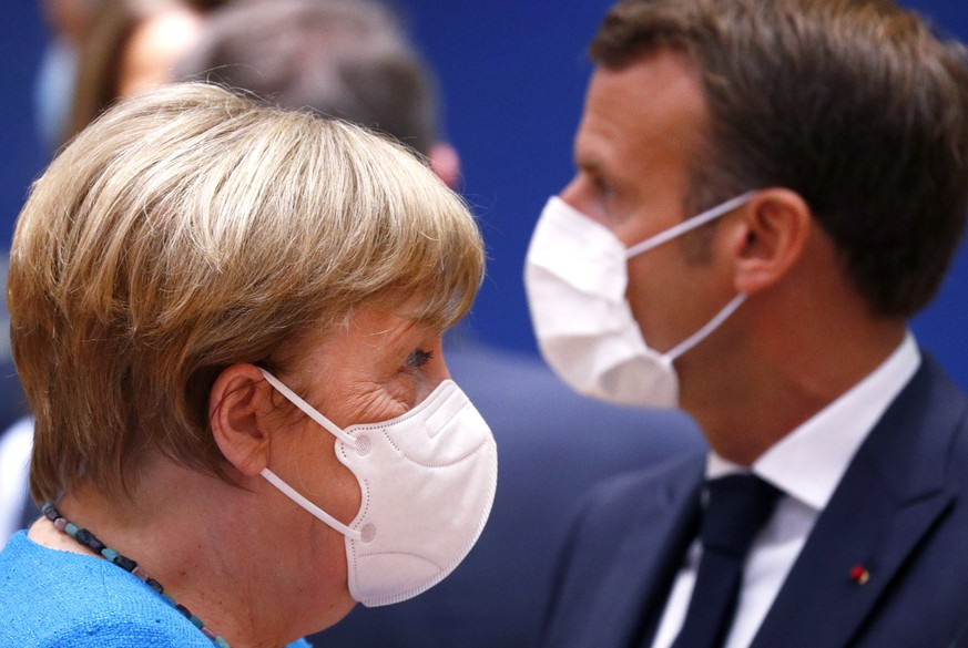 epa08553186 German Chancellor Angela Merkel (L) and France's President Emmanuel Macron (R), both wearing a face mask, at the start of the second day of an EU summit in Brussels, Belgium, 18 July 2020. European Union nations leaders meet face-to-face for the first time since February to discuss plans responding to coronavirus crisis and new long-term EU budget at the special European Council on 17 and 18 July.