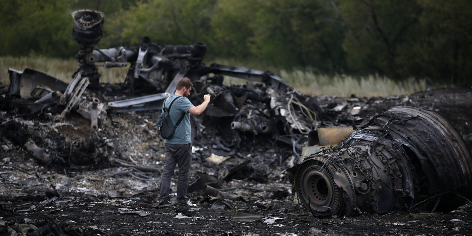 A journalist takes photographs at the site of Thursday's Malaysia Airlines Boeing 777 plane crash near the settlement of Grabovo, in the Donetsk region July 18, 2014. World leaders demanded an international investigation into the shooting down of Malaysia Airlines Flight MH17 with 298 people on board over eastern Ukraine, as Kiev and Moscow blamed each other for a tragedy that stoked tensions between Russia and the West.    REUTERS/Maxim Zmeyev (UKRAINE - Tags: POLITICS TRANSPORT DISASTER CIVIL UNREST MEDIA)
