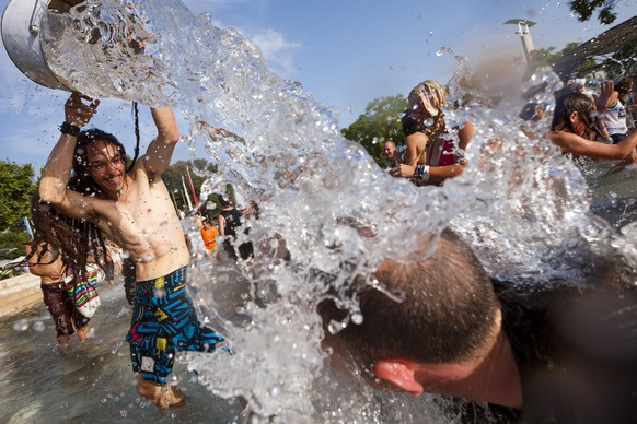 People throw water at each other during a 10-minute long water battle flash mob in Lausanne, Switzerland, Friday, July 3, 2015. The temperatures have been reaching over 35 degrees Celsius for several days in a row in Switzerland and the extreme heat-wave affecting Europe is expected to still last over the next week. (KEYSTONE/Valentin Flauraud)