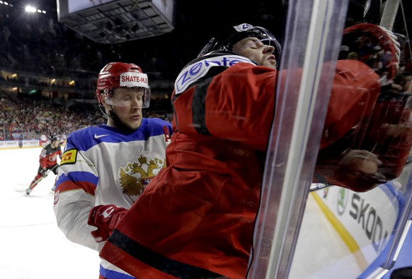 Russia's Sergei Andronov, left, checks Canada's Josh Morrissey at the Ice Hockey World Championships semifinal match between Canada and Russia in the LANXESS arena in Cologne, Germany, Saturday, May 20, 2017. (AP Photo/Petr David Josek)