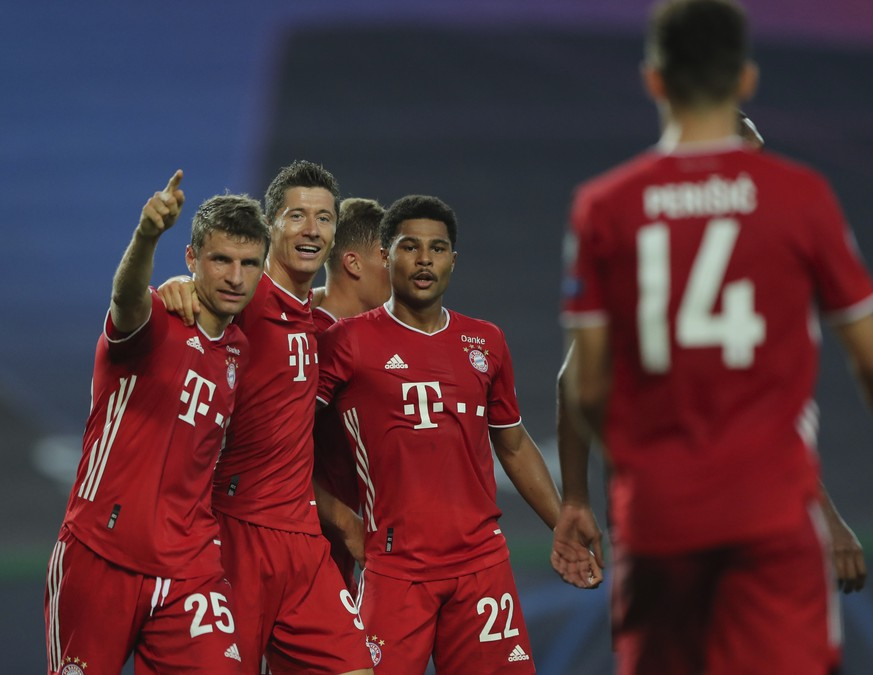 Bayern's Serge Gnabry, right, celebrates his side's second goal with teammates Robert Lewandowski, center, and Thomas Mueller during the Champions League semifinal soccer match between Lyon and Bayern Munich at the Jose Alvalade stadium in Lisbon, Portugal, Wednesday, Aug. 19, 2020. (Miguel A. Lopes/Pool via AP)