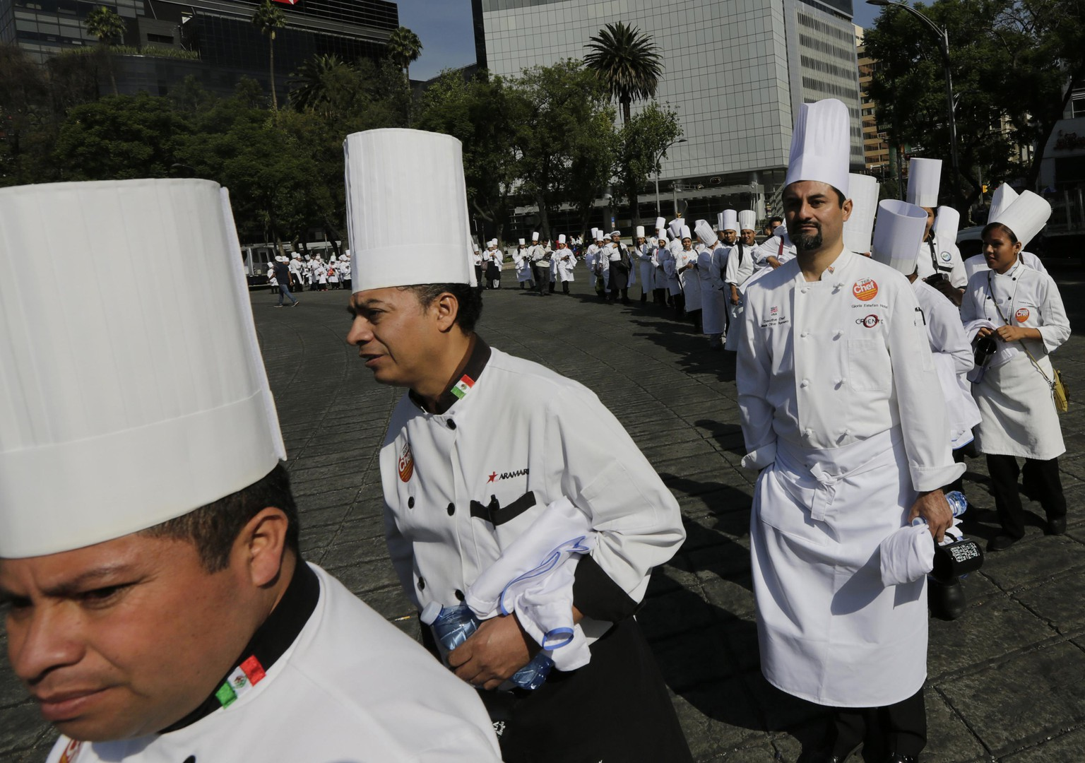 Chefs arrive to take part in a Guinness World Record-breaking gathering of 3,634 chefs and sommeliers at the Angel of Independence monument in Mexico City, May 17, 2014. The Mexico City tourism board said a Guinness World Records official confirmed the event had set a new world record of the largest number of chefs and sommeliers to gather in one place.  REUTERS/Henry Romero (MEXICO - Tags: SOCIETY)