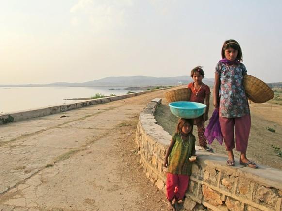Drei Mädchen stehen am 25.10.2015 am Fluss Ken in Panna (Indien). Vom Fluss Ken, der sich durch das Naturschutzgebiet mit seinen Tigern, Krokodilen, Geiern und zehn Stammesdörfern schlängelt, sind nur noch vereinzelte Tümpel übrig. Foto: Friederike Heine/dpa (zu dpa «Indien vernetzt Flüsse - Menschen und Tiger müssen weichen» vom 04.11.2015) +++(c) dpa - Bildfunk+++