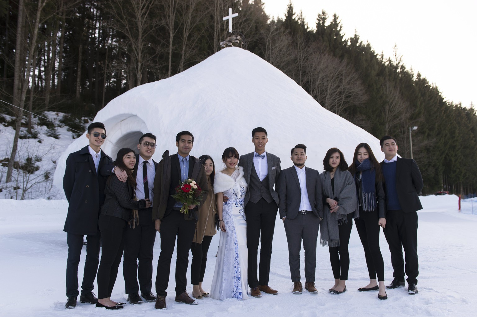 epa05793120 Newlyweds Chinese young people and their guests pose for a picture on the Valentine's Day, in the Swiss Alps Resort of Leysin, Switzerland, 14 February 2017. An ice church is a new attraction of the Swiss ski resort of Leysin, developed to attract Asian tourists, who want to get married in an ice church.  EPA/THOMAS DELLEY
