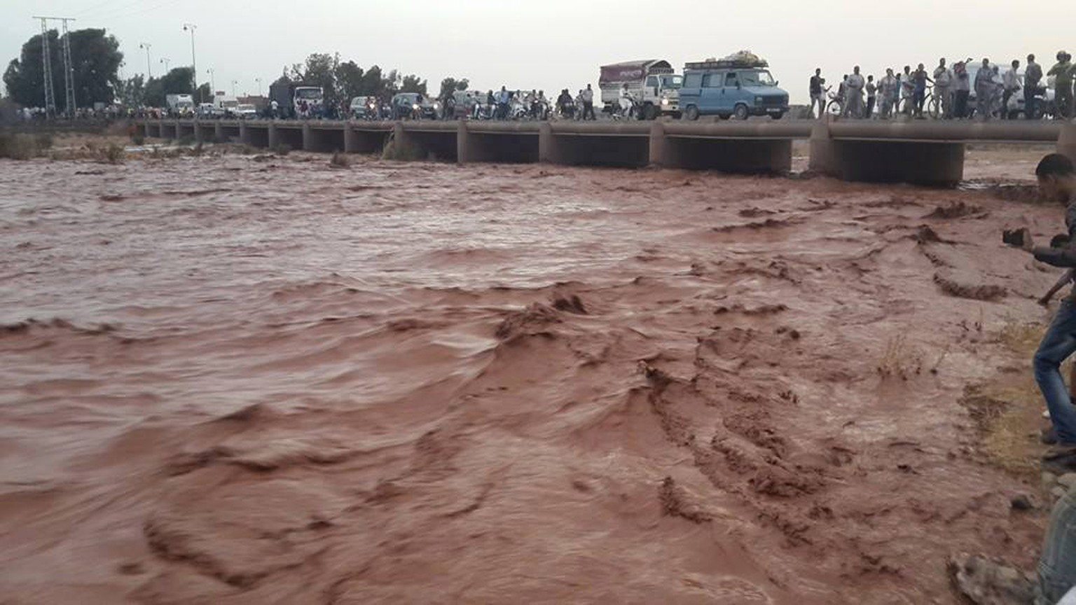 This image taken with a mobile phone shows residents of Guelmim, south western Morocco, crossing a bridge over floodwaters, Monday, Nov. 24, 2014. Morocco's government reports that heavy flooding in the south has killed at least 17 people with another 18 missing after heavy rains over the weekend. In the southern city of Guelmim alone, 13 people were killed by a flash flood that roared through a dry river bed, reported the Interior Ministry in a statement carried by the national news agency late Sunday. (AP Photo)