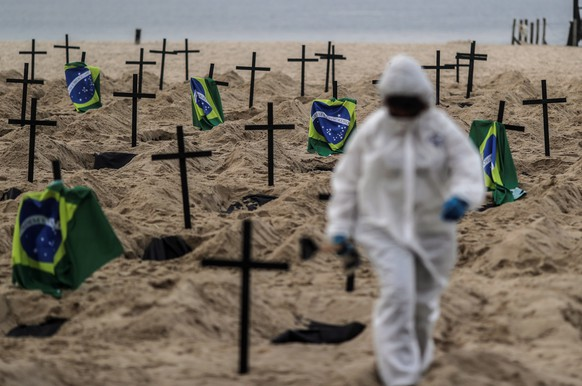 epaselect epa08479378 An Activist places one hundred and ten crosses, as a way of denouncing the errors made by the Government in managing the coronavirus crisis, during a protest organized by the NGO Rio de Paz, on Copacabana beach , Rio de Janeiro, Brazil, 11 June 2020.  EPA/ANTONIO LACERDA