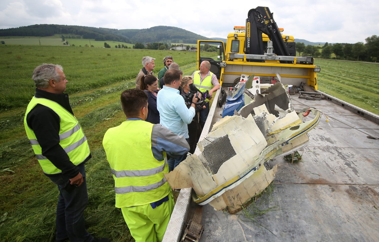 epa04278014 Journalists, officers of the Criminal Investigation Department and staff of a breakdown service stand next to a truck carrying wreckage near the sight of the crash of a Lear jet near Elpe, Germany, 24 June 2014. A Lear jet with two passengers crashed after colliding with a Eurofighter of the German Air Force over Olsberg. The Eurofighter was able to land at its base in Noervenich near Cologne after the collision.  EPA/MARCEL KUSCH