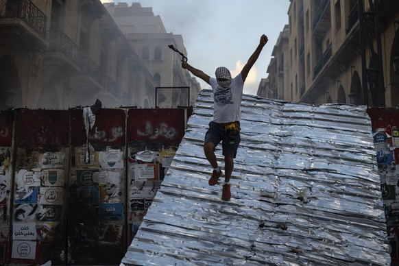 A man jumps from a barrier blocking the access to the parliament building during an anti-government protest, in the aftermath of last Tuesday's massive explosion which devastated Beirut, Lebanon, Monday, Aug. 10, 2020. (AP Photo/Felipe Dana)