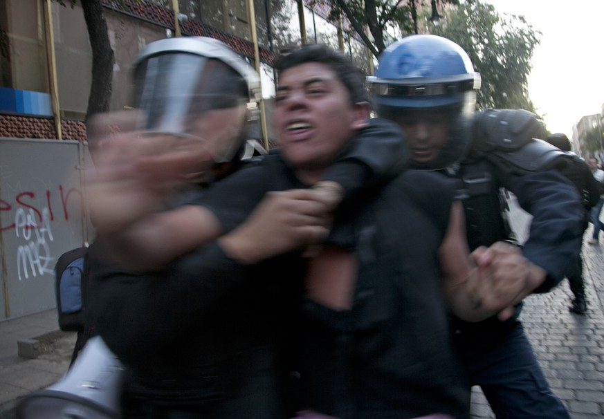 Riot police detain a protester as dozens of masked protestors clashed violently with police following a peaceful march commemorating the anniversary of the Tlatelolco massacre in Mexico City, Friday, Oct. 2, 2015. Mexico commemorated the 47th anniversary of the massacre where students and civilians where killed by the military and police on October 2, 1968. The events are considered part of the Mexican Dirty War when the government used its forces to suppress political opposition. The massacre occurred 10 days before the opening of the 1968 Summer Olympics in Mexico City. (AP Photo/Marco Ugarte)