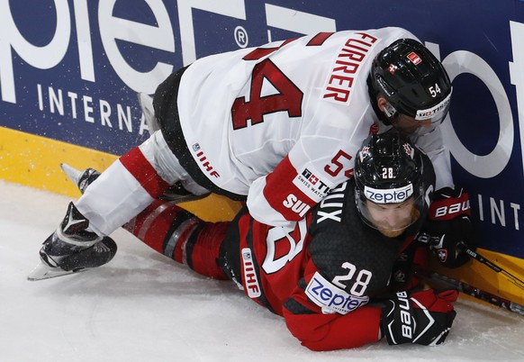 Switzerland's Philippe Furrer, top, checks Canada's Claude Giroux, bottom, during the Ice Hockey World Championships group B match between Canada and Switzerland in the AccorHotels Arena in Paris, France, Saturday, May 13, 2017. (AP Photo/Petr David Josek)