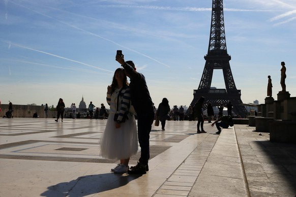 File - In this Thursday, March 30, 2017 file photo, tourists take a selfie on Trocadero with the Eiffel Tower in background on a sunny day in Paris. As of Thursday, June 15, 2017, European Union holiday makers can return home without a sense of anxiety about their mobile phone bill. The 28 EU nations should be a seamless area of roaming costs for travelers following years of negotiations to cut often excessive costs to use a mobile outside the home country. (AP Photo/Francois Mori, File)