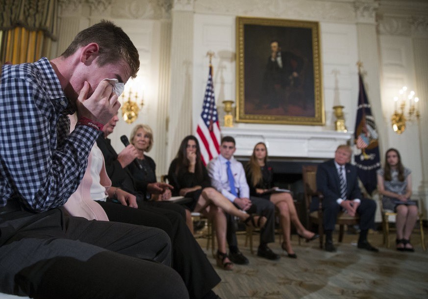 epa06551639 Marjory Stoneman Douglas High School shooting survivor Samuel Zeif (L) cries after delivering remarks as US President Donald J. Trump listens during a listening session with high school students and teachers in the State Dining Room of the White House in Washington, DC, USA, 21 February 2018. Families from the Parkland, Newtown and Columbine communities attended the meeting.  EPA/SHAWN THEW