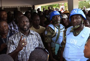 FILE-In this file photo taken on Wednesday, Nov. 9, 2011, opposition leader George Weah, left, is protected by United Nations peacekeepers from Nigeria as he speaks to supporters at opposition party headquarters in Monrovia, Liberia. President Ellen Johnson Sirleaf's son, who is running for a Senate seat, has filed a lawsuit contesting her Ebola-related ban on political rallies. Ahead of the Dec. 16, 2014,  election, the president banned gatherings in the capital, citing fears they could help spread Ebola. (AP Photo/Rebecca Blackwell, File)