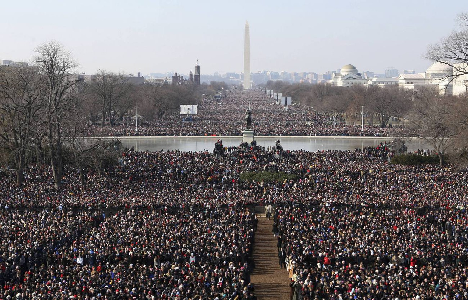 Crowds gather to watch the inauguration of President Barack Obama  Tuesday, Jan. 20, 2009, on the west side of the Capitol in Washington.  The Washington Monument can be seen in the background.   (AP Photo/Scott Andrews, Pool)