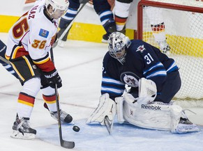 Calgary Flames' Raphael Diaz (36) looks for the shot on Winnipeg Jets goaltender Ondrej Pavelec (31) during third-period NHL hockey preseason game action in Winnipeg, Manitoba, Saturday, Oct. 4, 2014. (AP Photo/The Canadian Press, David Lipnowski)