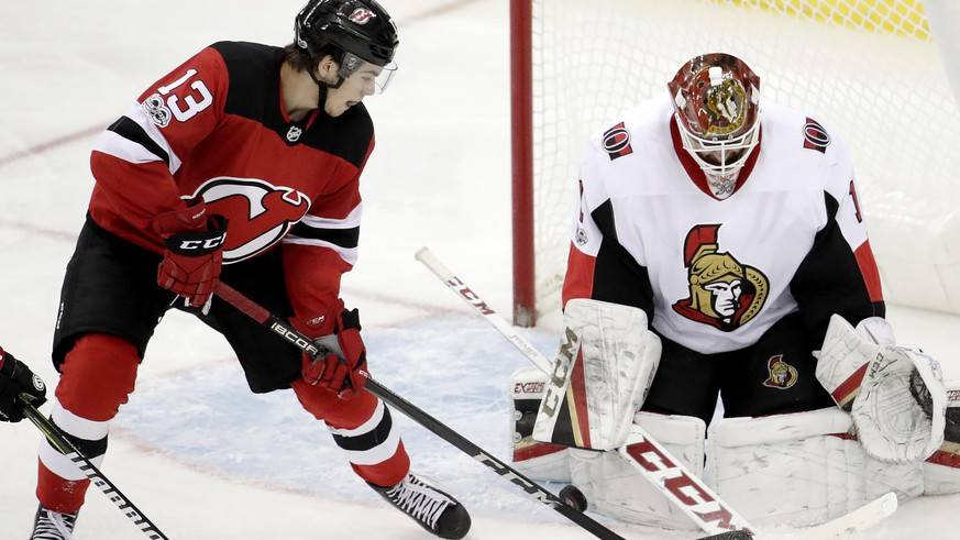 Ottawa Senators goalie Mike Condon (1) blocks a shot by New Jersey Devils center Nico Hischier (13), of Switzerland, during the third period of an NHL hockey game, Friday, Oct. 27, 2017, in Newark, N.J. (AP Photo/Julio Cortez)