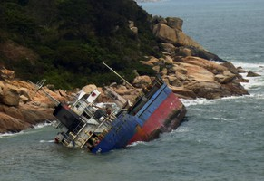 A cargo ship lies on its side after running aground on rocks off Cheung Chau island in Hong Kong February 21, 2014. All seventeen crew were rescued from the 90-metre Vietnamese-registered vessel, which was carrying cement from Nansha to Indonesia. The Marine Department said a floating barrier has been set up to contain an oil spill, government radio reported on Friday.  REUTERS/Stringer  (CHINA - Tags: DISASTER BUSINESS) NO SALES. NO ARCHIVES. FOR EDITORIAL USE ONLY. NOT FOR SALE FOR MARKETING OR ADVERTISING CAMPAIGNS
