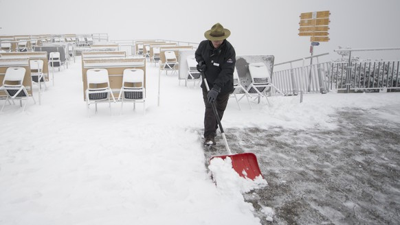 epa06283979 A man clears fresh snow that lies on the terrace of a restaurant on the Stanserhorn mountain, close to Stans, in Switzerland, 23 October 2017.  EPA/URS FLUEELER