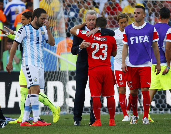 Switzerland's coach Ottmar Hitzfeld embraces player Xherdan Shaqiri after they were defeated in extra time in their 2014 World Cup round of 16 game against Argentina at the Corinthians arena in Sao Paulo July 1, 2014. REUTERS/Paul Hanna (BRAZIL  - Tags: SOCCER SPORT WORLD CUP)