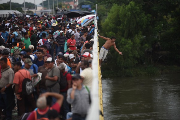 epaselect epa07107899 Honduran migrants jump in the Suchiate River in Tecun Uman, Guatemala, 20 October 2018, at the border between Mexico and Guatemala to enter Mexico while the immigration authorities keep the crossing closed.  EPA/EDWIN BERCIAN