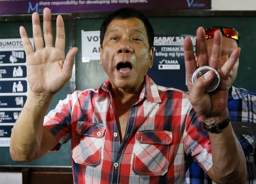 Front-running presidential candidate Mayor Rodrigo Duterte gestures at photographers to move back prior to voting in a polling precinct at Daniel R. Aguinaldo National High School at Matina district, his hometown in Davao city in southern Philippines Monday, May 9, 2016. Duterte was the last to vote among five presidential hopefuls. (AP Photo/Bullit Marquez)