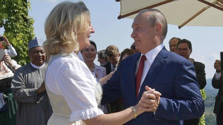 Russian President Vladimir Putin, right, congratulates Austrian Foreign Minister Karin Kneissl as he attends the wedding of Kneissl with Austrian businessman Wolfgang Meilinger in Gamlitz, southern Austria, Saturday, Aug. 18, 2018. (Alexei Druzhinin, Sputnik, Kremlin Pool Photo via AP)