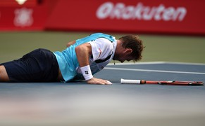 Top-seeded Stan Wawrinka of Switzerland falls on the court during the men's singles first round match against Tatsuma Ito of Japan at the Japan Open tennis tournament in Tokyo on September 30, 2014.       AFP PHOTO / TOSHIFUMI KITAMURA