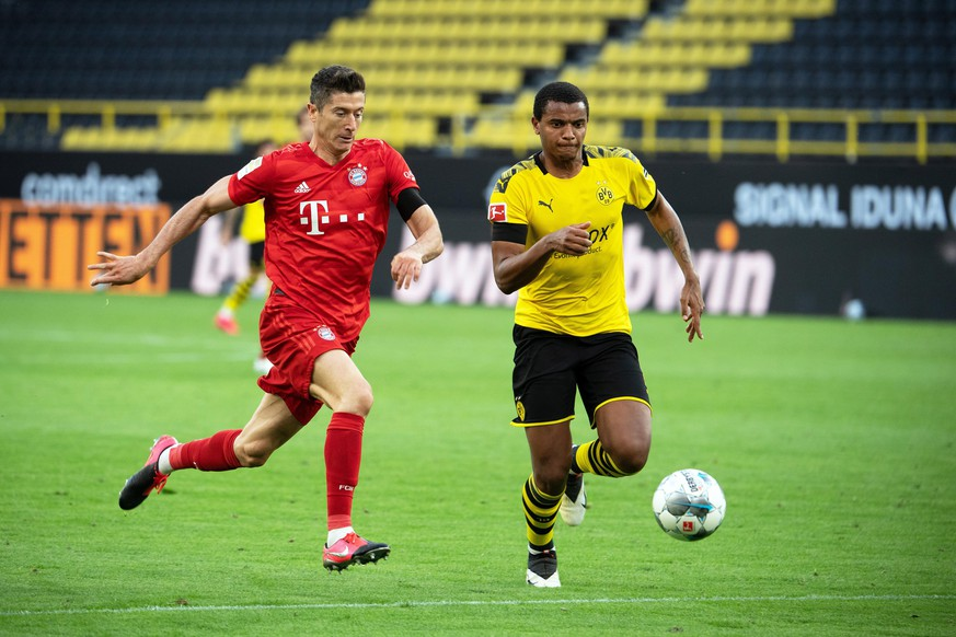 epa08446031 Bayern Munich's Robert Lewandowski (L) in action against Dortmund's Manuel Akanji (R) during the German Bundesliga soccer match between Borussia Dortmund and FC Bayern Munich at Signal Iduna Park in Dortmund, Germany, 26 May 2020. Bayern Munich won 1-0.  EPA/FEDERICO GAMBARINI / POOL ATTENTION: The DFL regulations prohibit any use of photographs as image sequences and/or quasi-video.