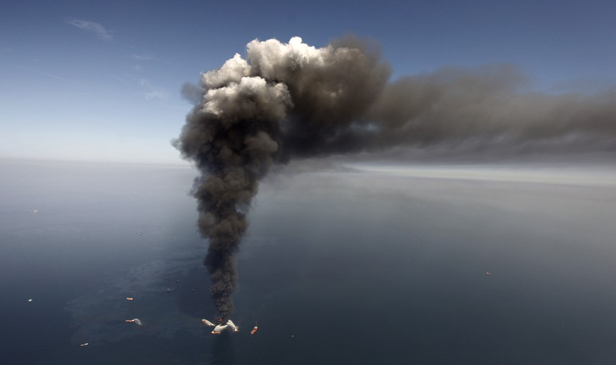 FILE -  In this April 21, 2010 file photo, oil can be seen in the Gulf of Mexico, more than 50 miles southeast of Venice on Louisiana's tip, as a large plume of smoke rises from fires on BP's Deepwater Horizon offshore oil rig. A week shy of the fifth anniversary of the Deepwater Horizon oil spill, the Obama administration proposed new regulations Monday aimed at strengthening oversight of offshore oil drilling equipment and ensuring that out-of-control wells can be sealed in an emergency.  (AP Photo/Gerald Herbert, File)