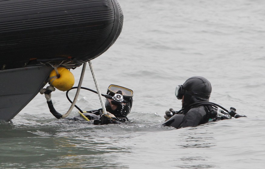 JINDO-GUN, SOUTH KOREA - APRIL 19:  Divers with the South Korean Navy search for missing passengers at the site of the sunken ferry off the coast of Jindo Island on April 19, 2014 in Jindo-gun, South Korea. At least twenty nine people are reported dead, with 267 still missing. The ferry identified as the Sewol was transporting about 475 passengers, including students and teachers, travelling to Jeju Island.  (Photo by Chung Sung-Jun/Getty Images)