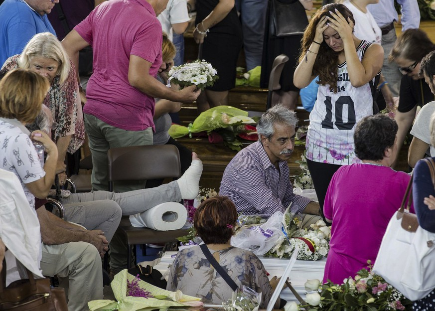 A woman holds her head as she looks at a coffin laid out in state, Saturday, Aug. 27, 2016, before the start of the mass funerals in Ascoli Piceno, central Italy, for some of the victims of a major earthquake that devastated a large area in central Italy. Residents of an Italian region devastated by an earthquake were rattled by a series of aftershocks overnight, the strongest measuring 4.2, as Italy began a day of national mourning on Saturday.(Massimo Percossi/ANSA via AP)