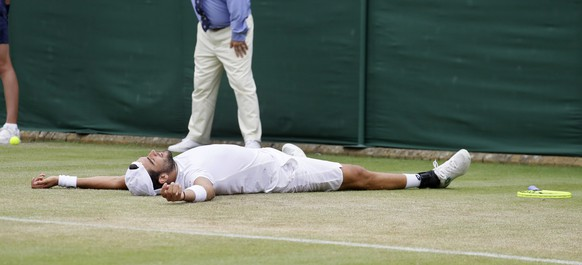 Italy's Matteo Berrettini falls to the ground as he celebrates after beating Argentina's Diego Schwartzman in a Men's singles match during day six of the Wimbledon Tennis Championships in London, Saturday, July 6, 2019. (AP Photo/Kirsty Wigglesworth)