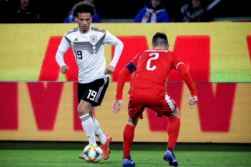 epa07451615 Germany's Leroy Sane (L) in action against Serbia's Antonio Rukavina (R) during the international friendly soccer match between Germany and Serbia in Wolfsburg, Germany, 20 March 2019.  EPA/FOCKE STRANGMANN CONDITIONS - ATTENTION: DFB regulations prohibit any use of photographs as image sequences and/or quasi-video.