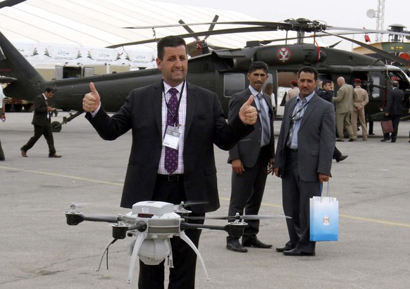 epa04193896 A US exhibitor thumps up for a Quadcopter at the opening of the Special Operations Forces Exhibition (SOFEX) arms fair in Amman, Jordan, 06 May 2014. Some 371 defense companies from 35 countries participate in the event to demonstrate their latest high-tech military industry equipment as well as innovations and training and organizational techniques related to security agencies and peacekeeping forces.  EPA/JAMAL NASRALLAH