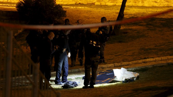 Israel police stand next to the dead body of a Palestinian man who was shot dead by Israeli security after he opened fire towards Israeli security force just outside Jerusalem's Old city, police said February 14, 2016. REUTERS/Ammar Awad