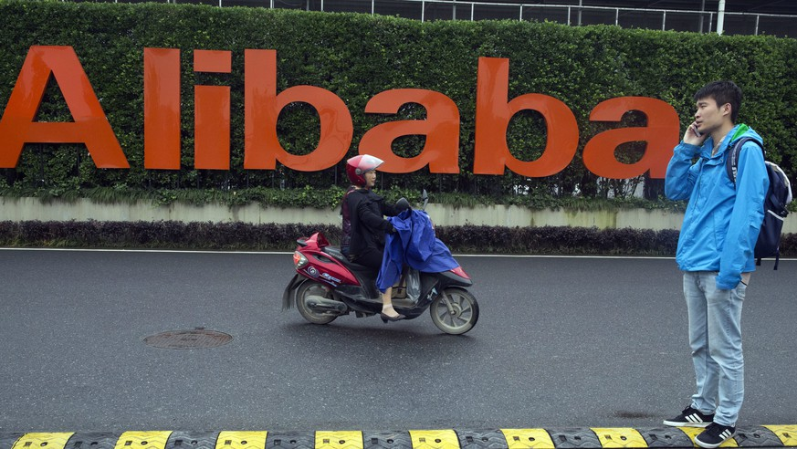 FILE - In this Friday, May 27, 2016, file photo, a man talks on his phone as a woman rides on an electric bike past a company logo at the Alibaba Group headquarters in Hangzhou in eastern China's Zhejiang province. Ford Motor Co. is collaborating with Chinese e-commerce giant Alibaba Group to further expand into the world's largest auto market. The carmaker signed a three-year agreement that will investigate ways to use technology for marketing, sales, cloud computing, and distribution strategies. It hopes to better incorporate digital technologies and platforms into its vehicles. (AP Photo/Ng Han Guan, File)