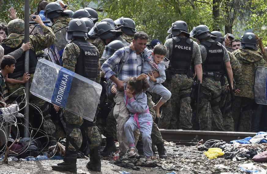 epa04893022 Migrants break through the cordon of Macedonian special police forces to cross into Macedonia near the southern city of Gevgelija, The Former Yugoslav Republic of Macedonia, 22 August 2015. Macedonian security forces strengthened the barricades along the Greek border 22 August, where thousands of refugees from the Middle East were stranded after a hot day and a rainy, chilly night, local media reported.  EPA/GEORGI LICOVSKI