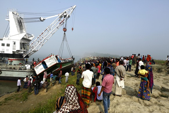 epa04633565 epa04633563 A large crowd gathers near Manikganj, western Bangladesh 23 February 2015 as the ferry that capsized in the Padma River 22 Feb is brought ashore.  So far 69 bodies have been recovered out of the 150 passengers who were on board at the time of the collision with a cargo vessel.  EPA/ABIR ABDULLAH  EPA/ABIR ABDULLAH