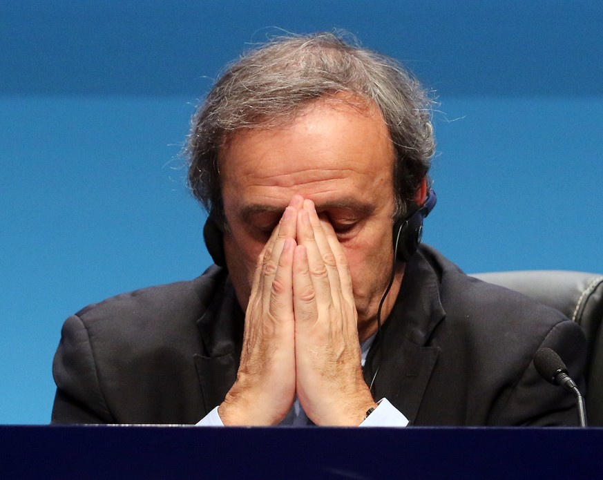 FILE - In this March 24, 2015 file photo UEFA President Michel Platini covers his face during a news conference at the end of the 39th Ordinary UEFA Congress in Vienna, Austria. The Court of Arbitration for Sport, CAS, in Lausanne, Switzerland, plans to announce its verdict on Monday, May 9, 2016 in Michel Platini's appeal on his six-year ban from football. (AP Photo/Ronald Zak, file)