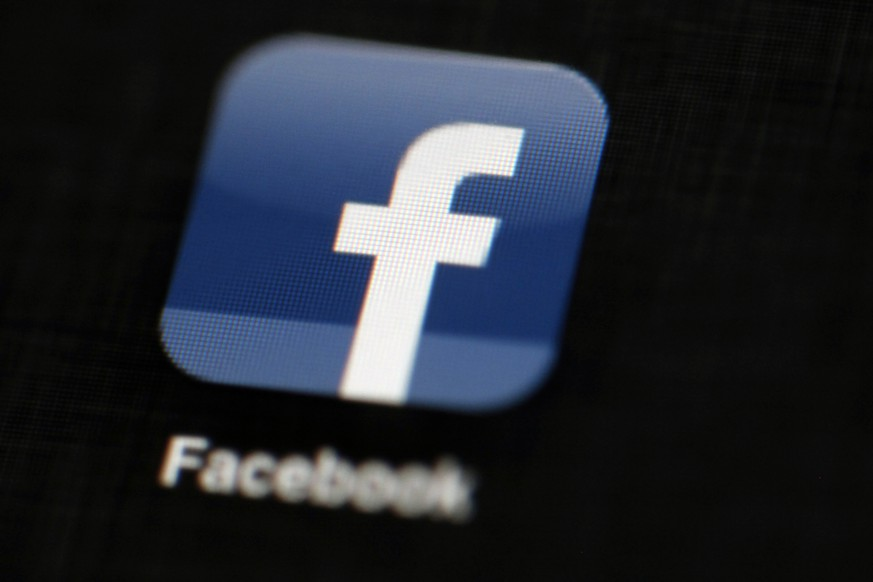 FILE - In this May 16, 2012, file photo, the Facebook logo is displayed on an iPad in Philadelphia.  Facebook suspended Cambridge Analytica, a data-analysis firm that worked for President Donald Trump's 2016 campaign, over allegations that it held onto improperly obtained user data after telling Facebook it had deleted the information.  (AP Photo/Matt Rourke, File)