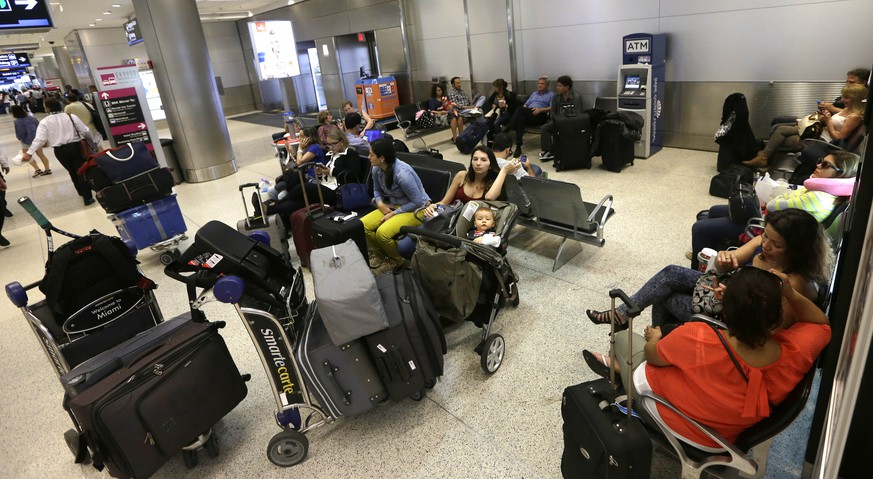 Travelers wait to board their flights at Miami International Airport in Miami, Tuesday, Nov. 25, 2014. Thanksgiving travelers along the East Coast were heading out early because of a forecast calling for a nor'easter that will bring rain and snow. All the major U.S. airlines were closely monitoring the situation but have not yet canceled flights. (AP Photo/Alan Diaz)