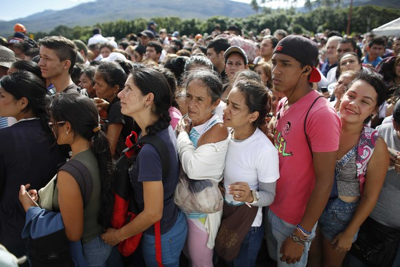 Venezuelans wait in line to cross into Colombia through the Simon Bolivar bridge in San Antonio del Tachira, Venezuela, Sunday July 17, 2016. Tens of thousands of Venezuelans crossed the border into Colombia on Sunday to hunt for food and medicine that are in short supply at home. It's the second weekend in a row that Venezuela's government has opened the long-closed border connecting Venezuela to Colombia. (AP Photo/Ariana Cubillos)